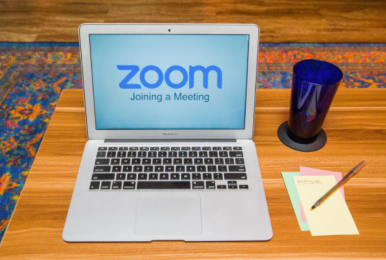 macbook with zoom logo with pens, notepad on wooden desk on rug